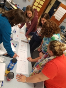 Teachers investigating graphs on a table